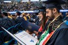 ziz Aldasem reads his diploma after walking during the College of Business and Economics Commencement in the Coliseum.