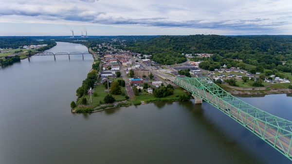 arial view of two rivers meeting at a point of land with a green bridge spanning waterway to the left