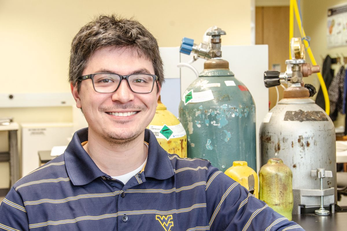 Man wearing a striped WV shirt and glasses sitting in a laboratory.