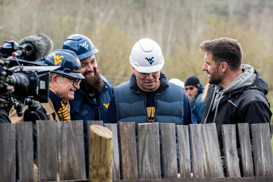 Men in WVU hardhats stand behind a wooden fence. A video camera is to their right.
