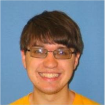 Headshot of boy with glasses and brown hair smiling in a yellow shirt