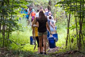 Freshmen Honors students carry buckets, shovels and other supplies as they walk into the Core Arboretum in August 2016 to participate in their Service Day.