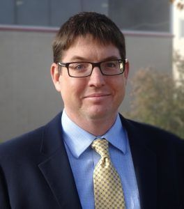 Smiling man in a suit and tie with glasses.