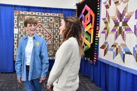 two women stand near hanging quilts
