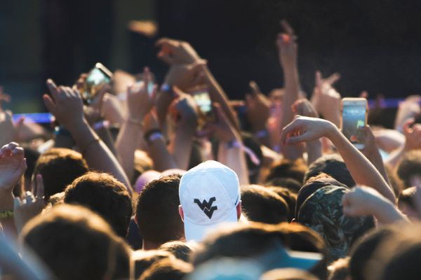 crowd with arms raised facing a stage