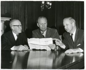 Photo in black and white of three men at a table.