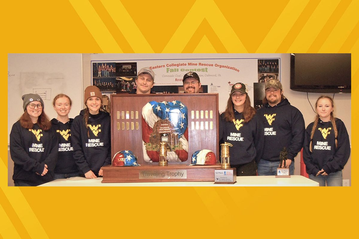 A group of college students stand behind an award; the photo is on a gold background