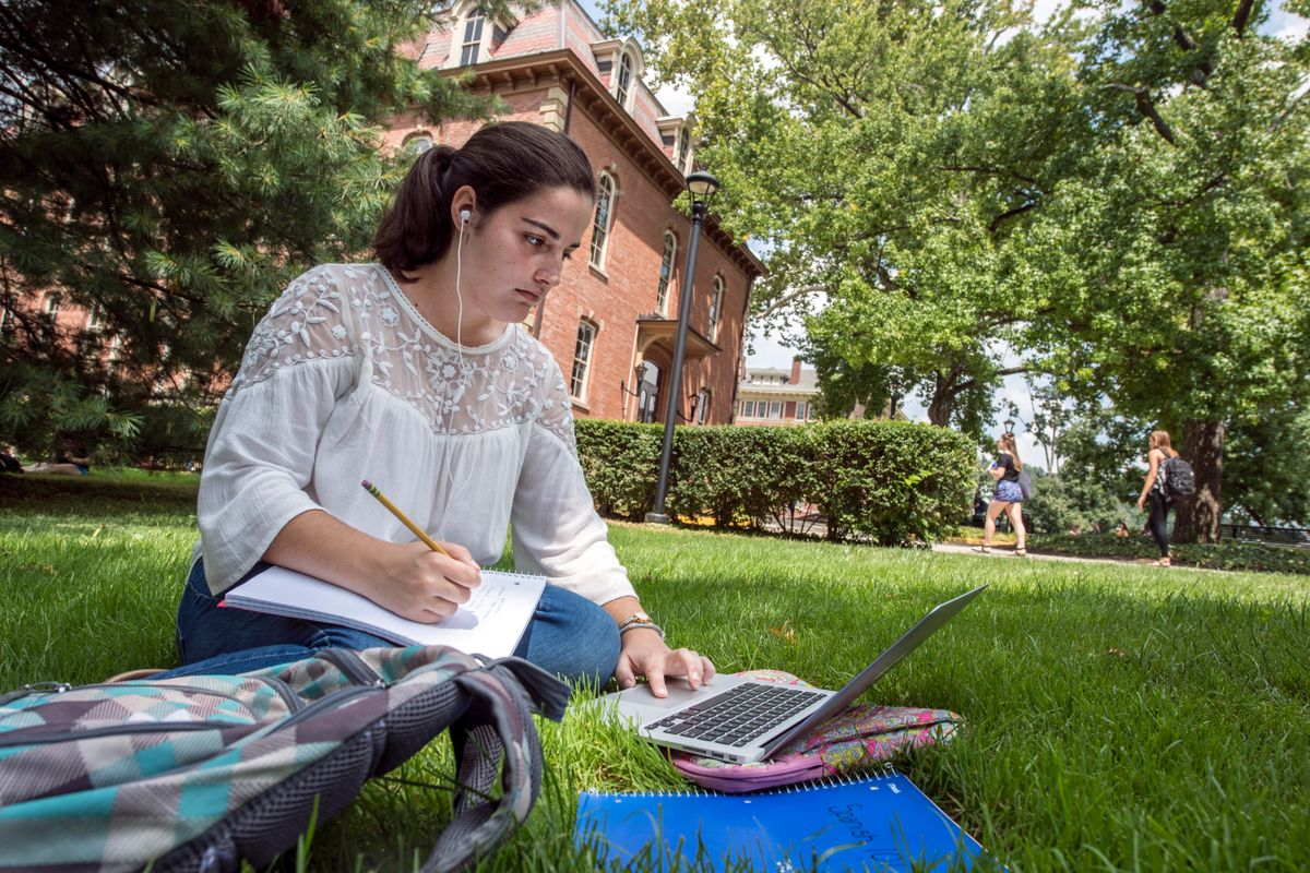 a young woman sits in the shade on the grass taking notes, looking at a laptop