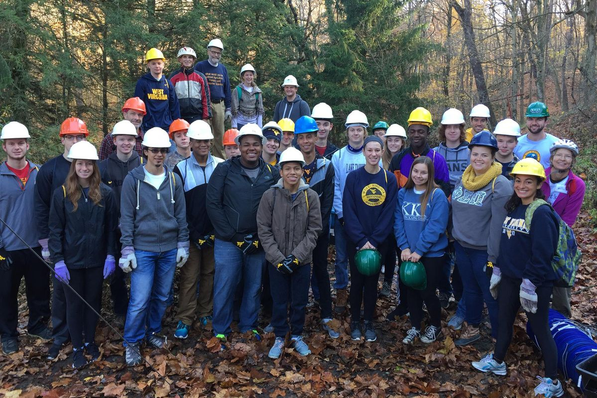 group of students in forest wearing hard hats