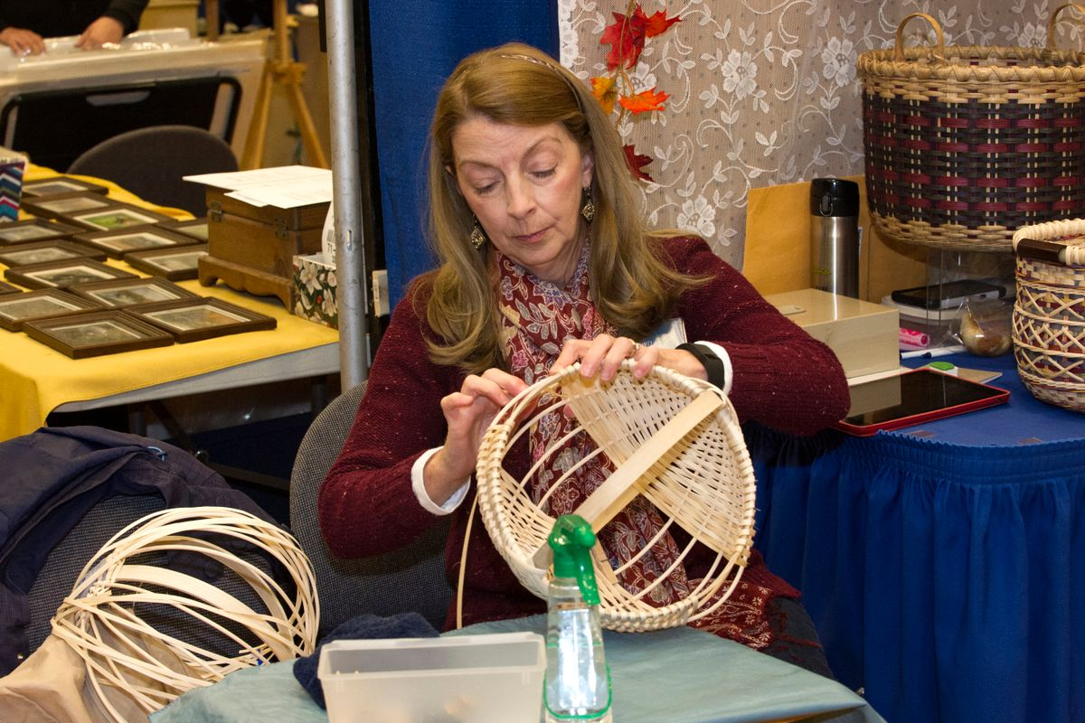 A woman with long brown hair in a burgundy sweater and scarf weaving a basket together sitting at a craft table.