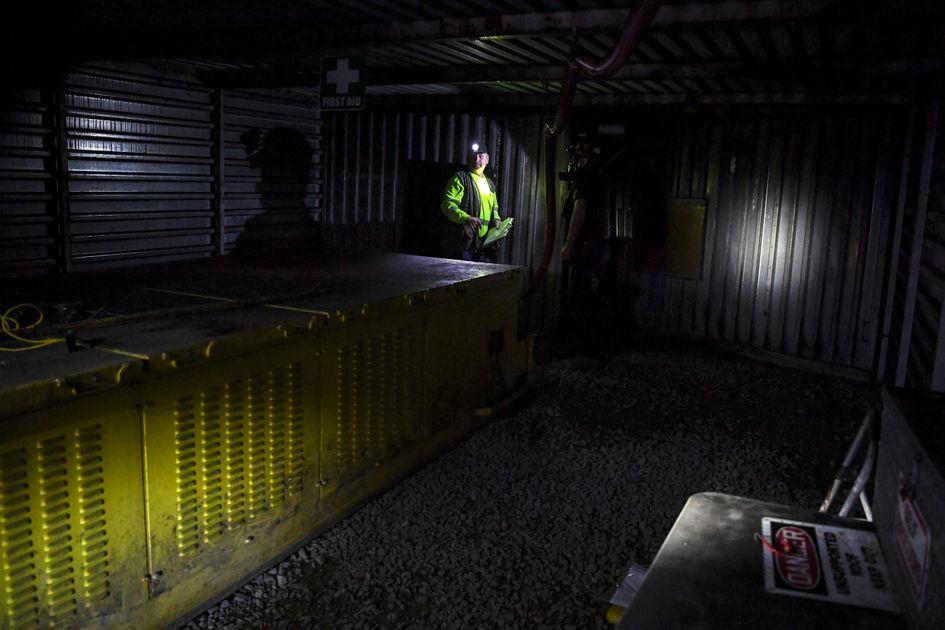 a coal miner stands in dim light of a mine