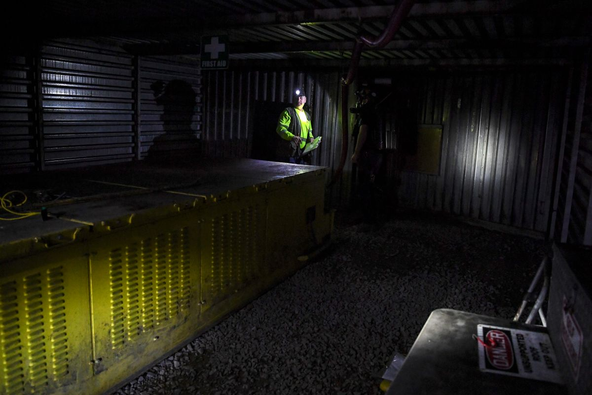 a coal miner stands in dim light of a mine