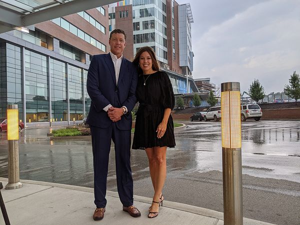 Smiling man in suit stands next to smiling woman in dress in front of WVU Hospital