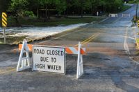 A road closed to due to high water sign attached to a sawhorse sits in front of a flooded roadway.