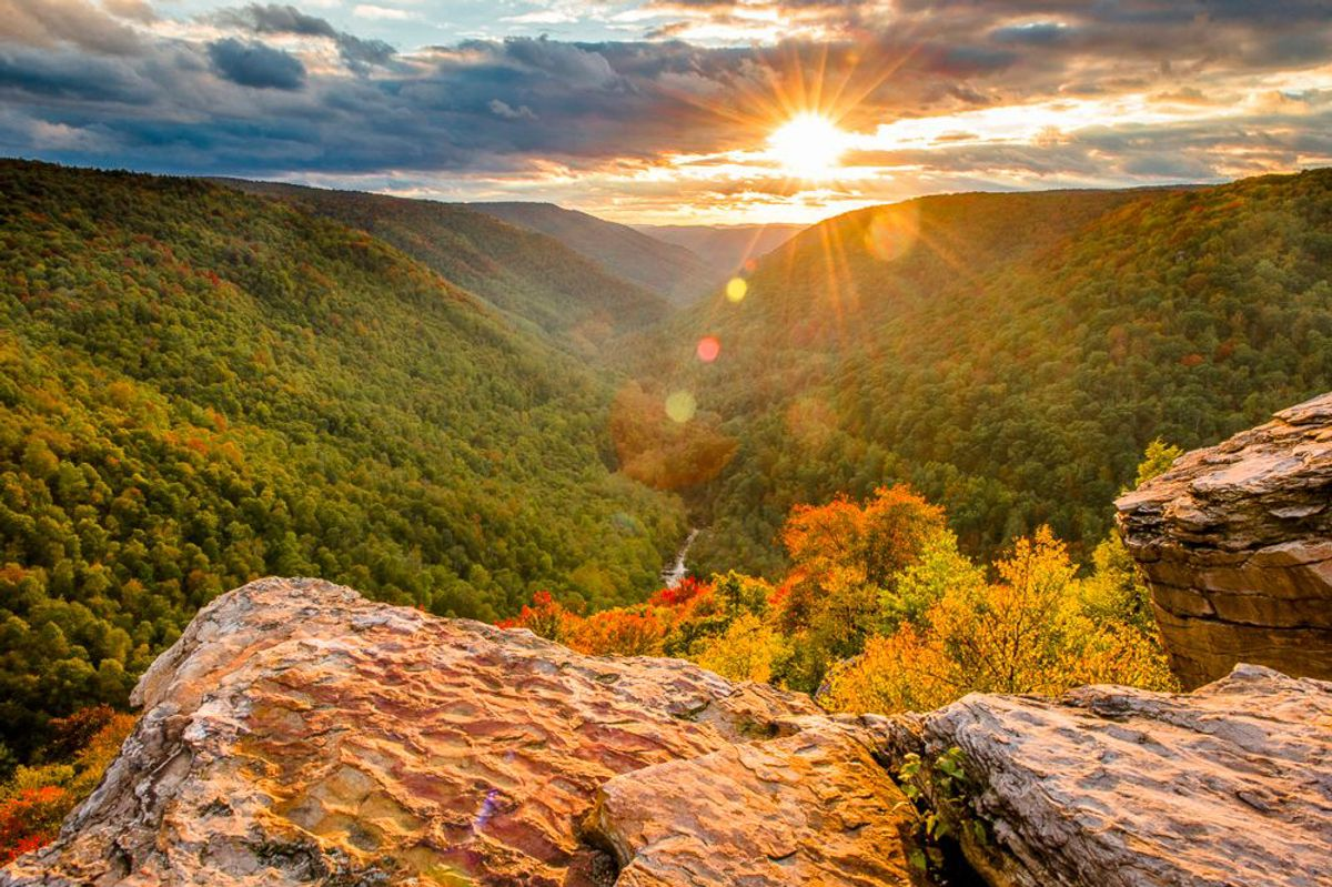 An overview of mountains, trees, rocks, and a sunset