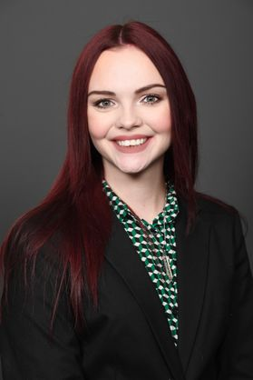 Professional headshot of young woman with red hair smiling in green blouse and black blazer