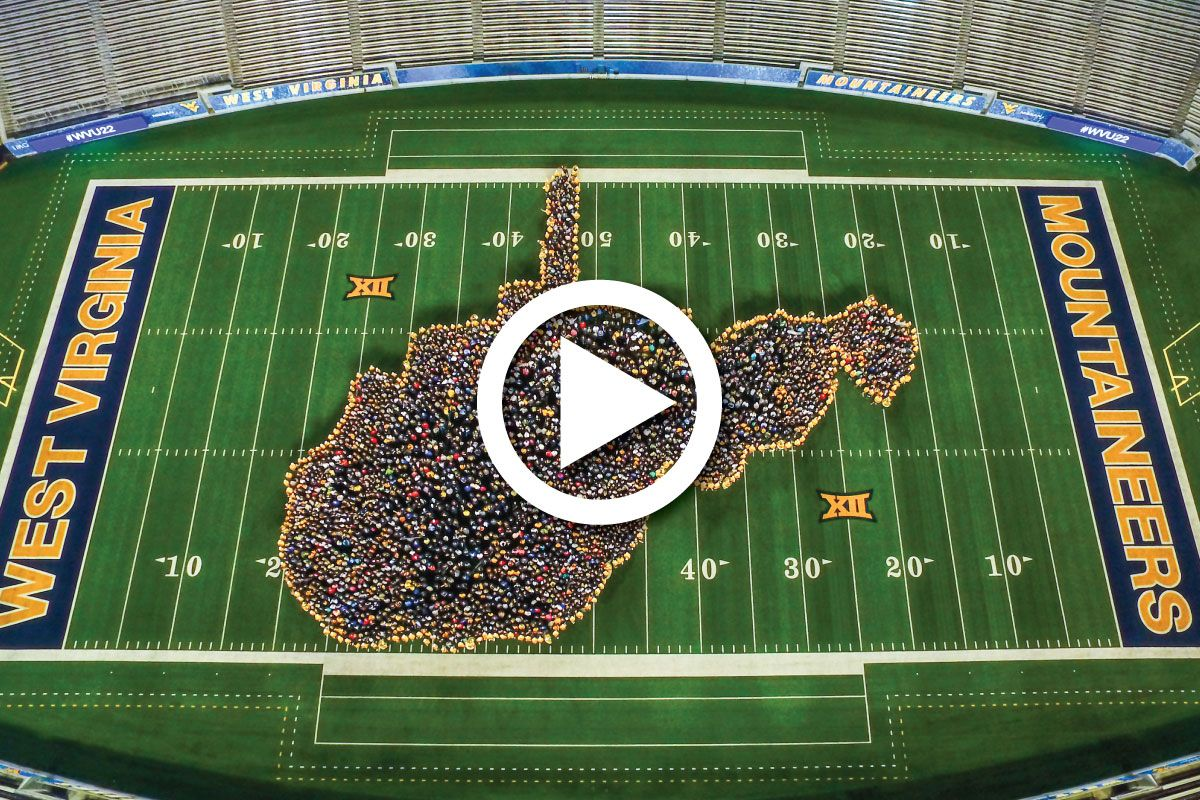 Milan Puskar Stadium from above with a crowd of new WVU students forming the outline of the state of West Virginia on the field.