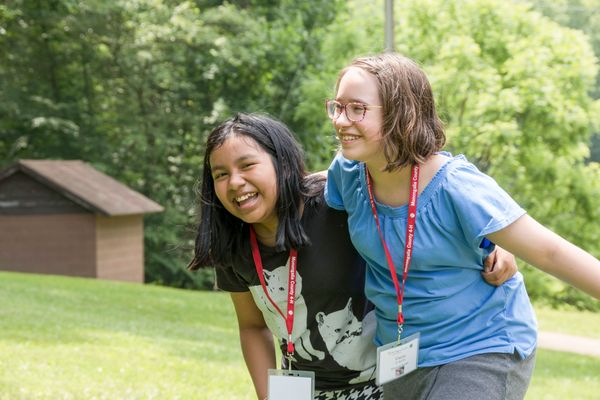 Two young girls smile and embrace at 4-H camp