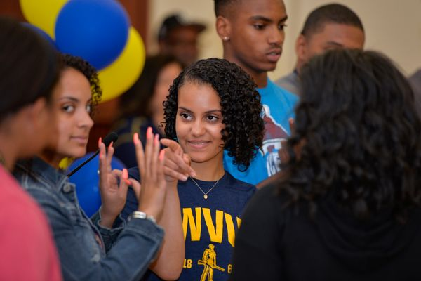 Young woman in WVU shirt stands in group of other young people