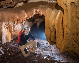 A woman looks at a cave formation in artificial lighting