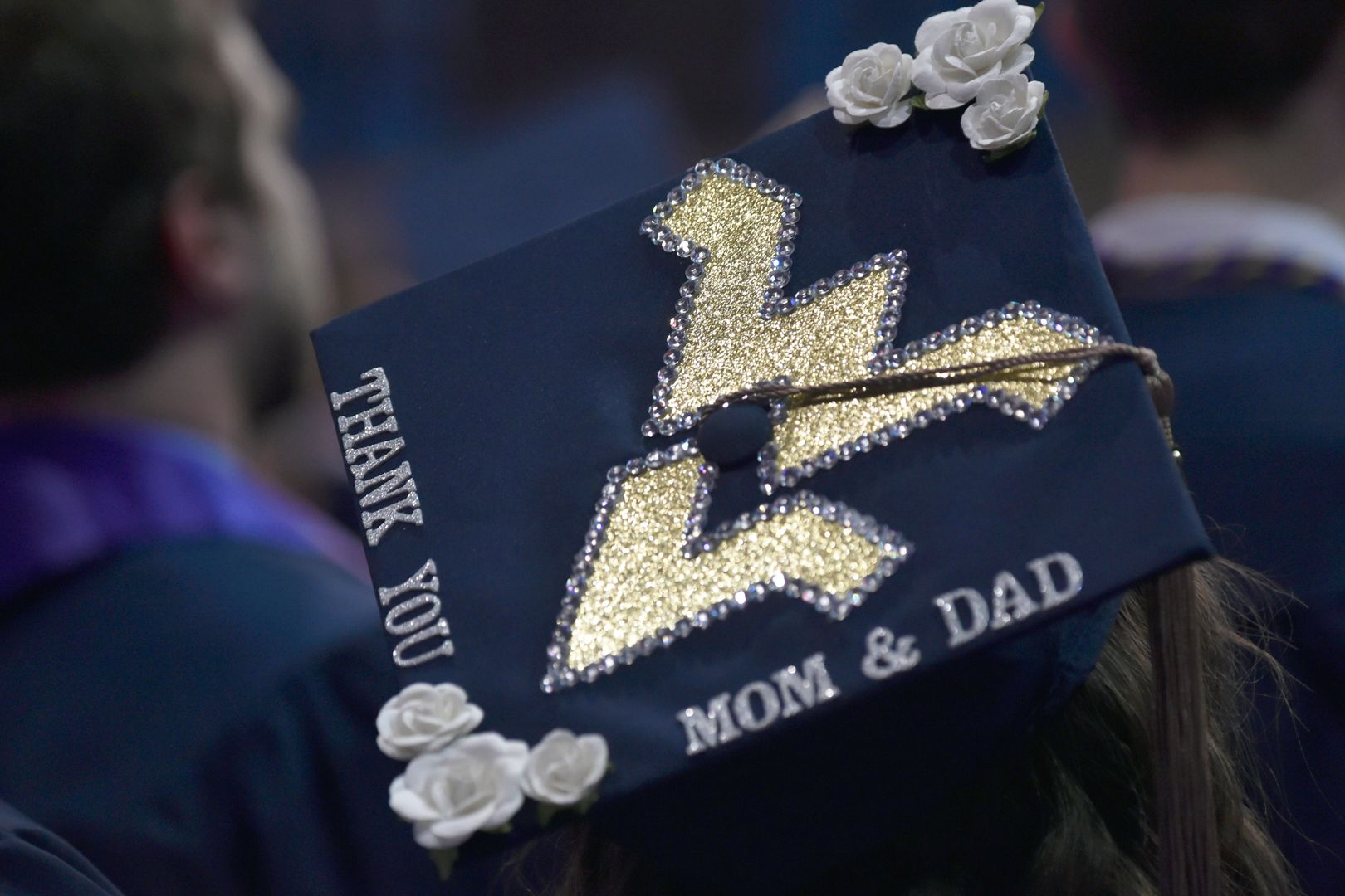 """Photo of the back of a navy blue WV graduation cap decorated with a big flying WV and the words """"Thank you mom & dad"""" written on the boarder."""