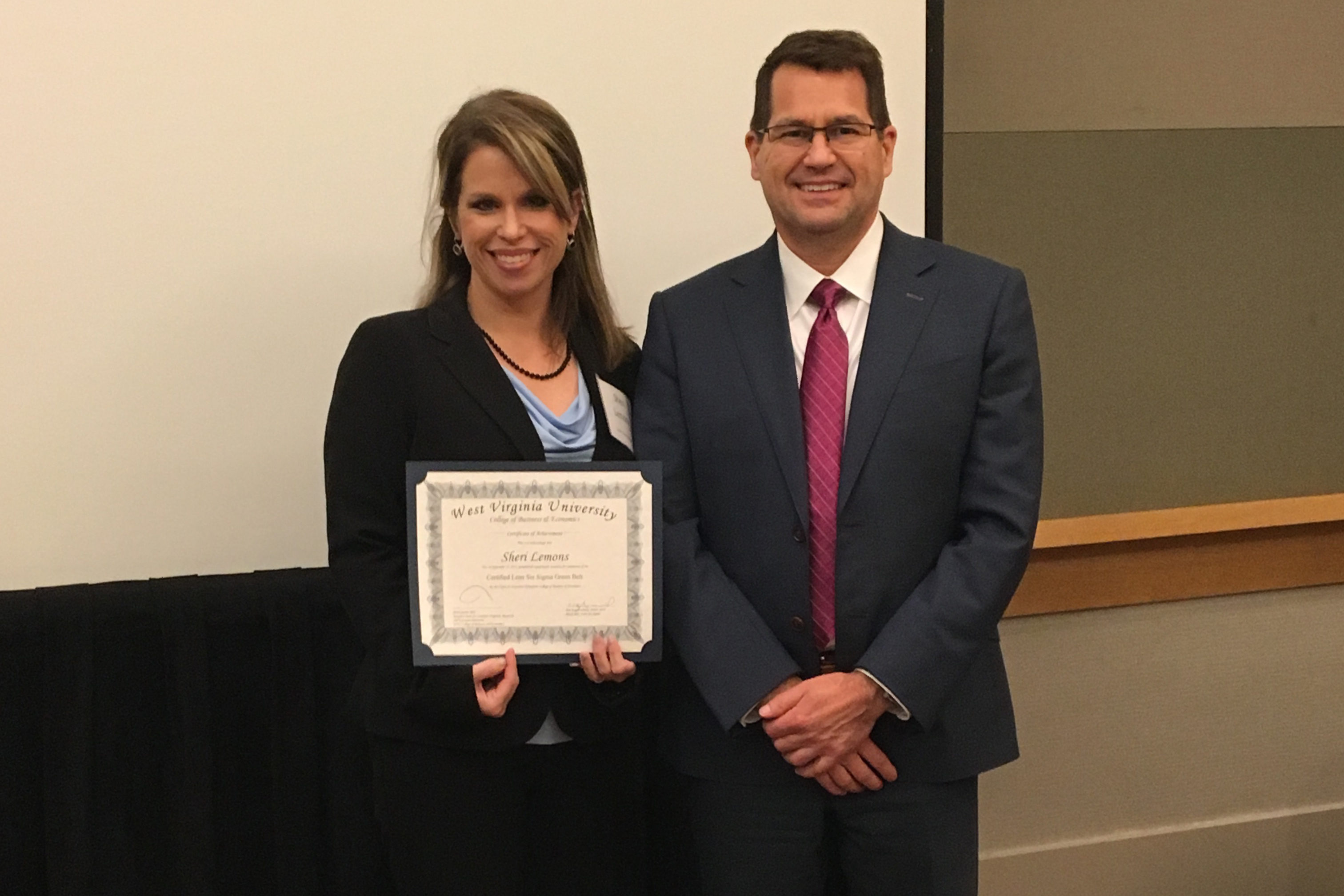 Sheri Lemons shows her certificate from the Lean Six Sigma Green Belt program in the WVU College of Business and Economics.Tim Kupferschmid is the instructor for the LSS course.