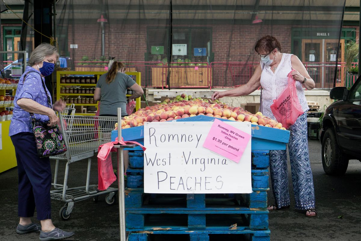 women in masks look at peaches