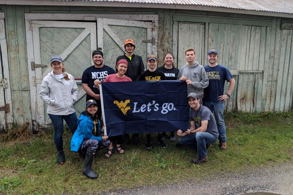 A group of WVU engineering students stand in front of an old building holding a