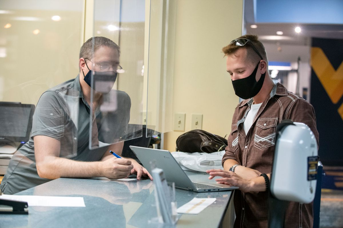 masked people sit face to face with plexiglass screen between them