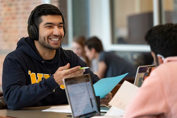 smiling man sits across from man with laptop