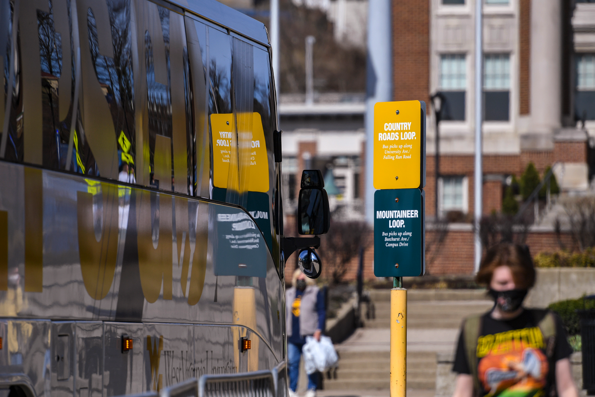 The reflection of traffic signs on the side of a WVU bus.
