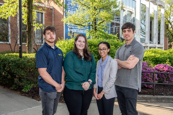 photo of four young people standing outside