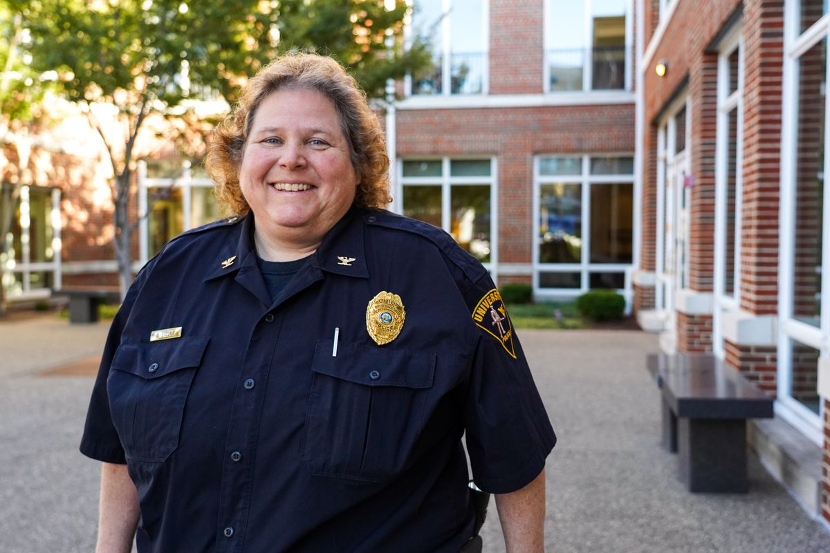 Woman in police uniform stands outside in front of a brick building