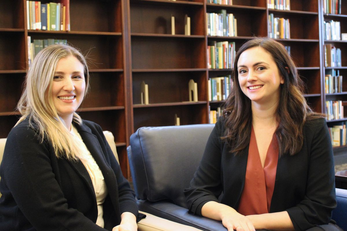 two women in black sweaters sit in front of bookshelves
