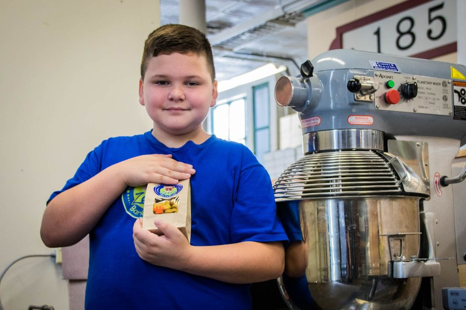 A boy in a blue t-shirt holds a package. He is standing by a dehydrator.