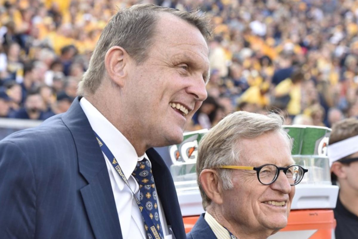 President Gee and Shane Lyons stand at the football field wearing blue suits looking to the right of the frame