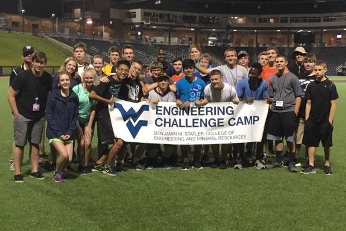 Boys and girls standing with WV Engineering Challenge Camp banner