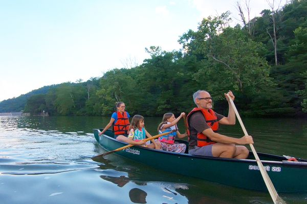 photo of two adults and two children canoeing on a river