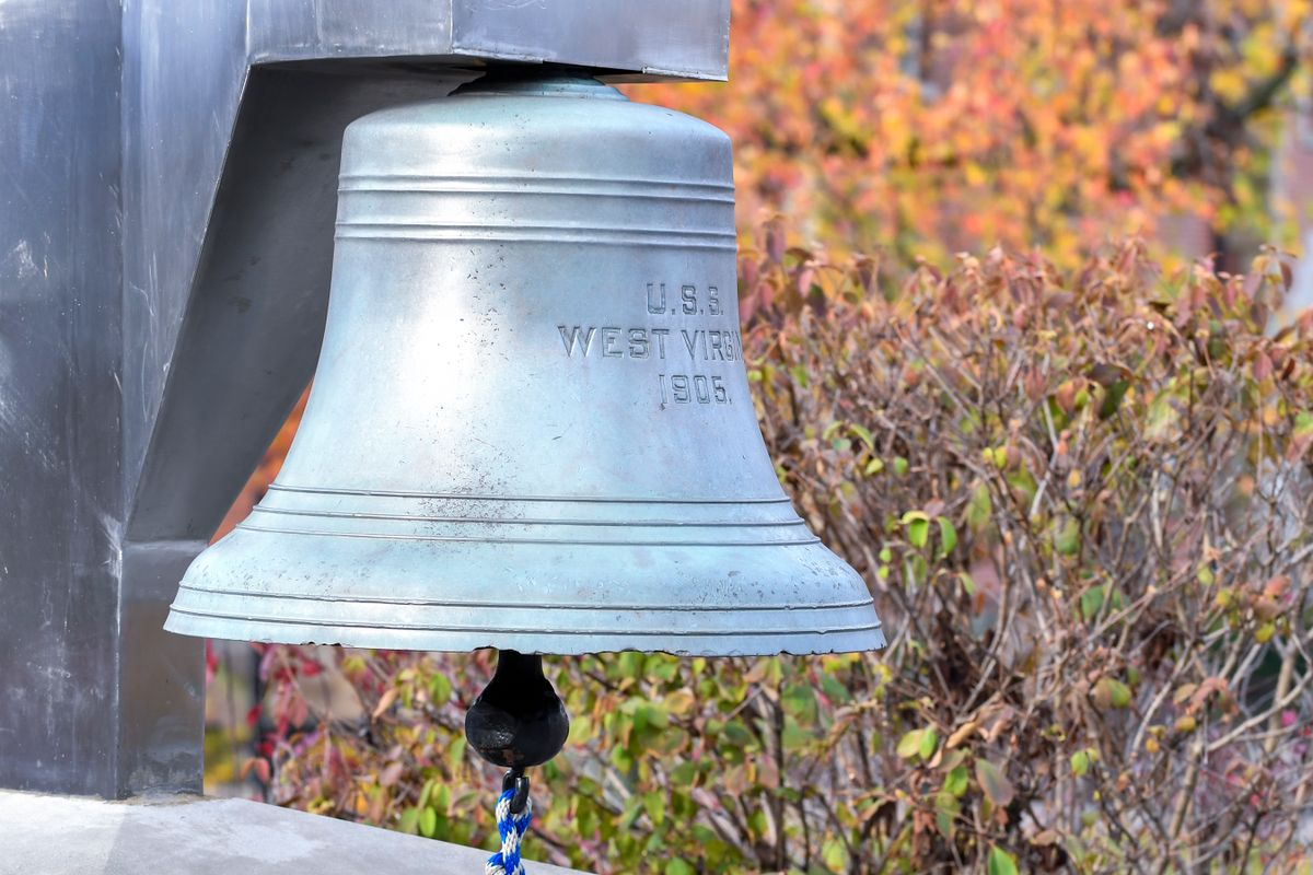 large bell, engraved, fall leaves in background