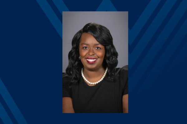 Headshot of smiling Black woman in pearls and black dress on blue background