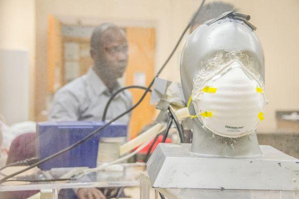 Man working with a mannequin that has a mask on it