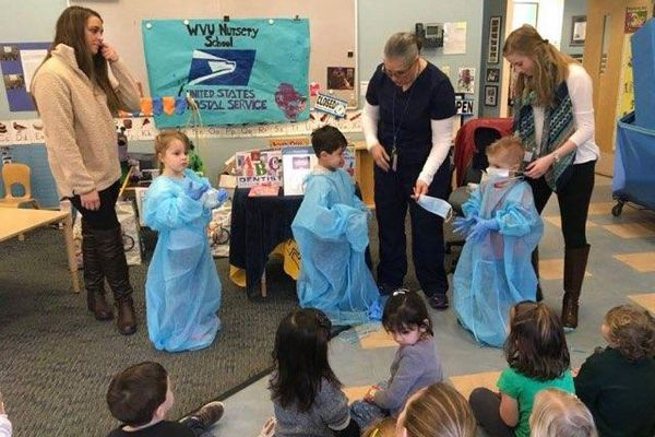 adults work with kids dressed in scrubs gowns