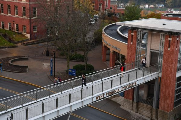 Students walk across the pedestrian bridge from the WVU College of Business and Economics.