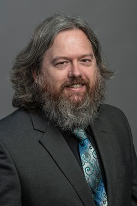 photo of fully bearded man wearing gray jacket, black shirt iridescent green and blue tie