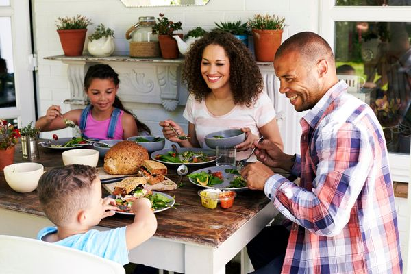 Family sits at table eating food