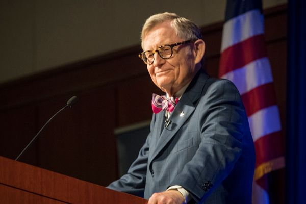 Man in a bow tie and glasses stands behind podium, in front of American flag
