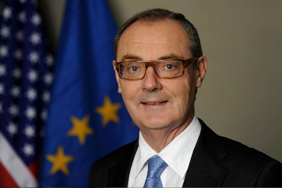 A man wearing glasses and a suit coat and tie in front of flags