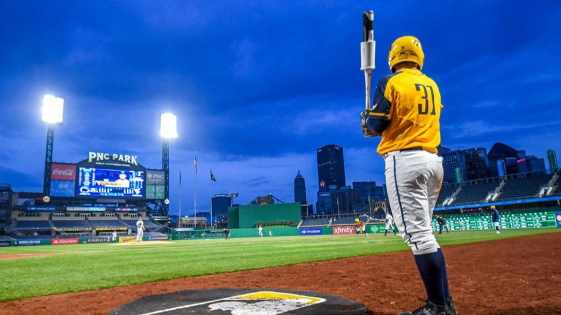 Baseball player stands in dark blue sky on a baseball field with yellow jersey holding bat