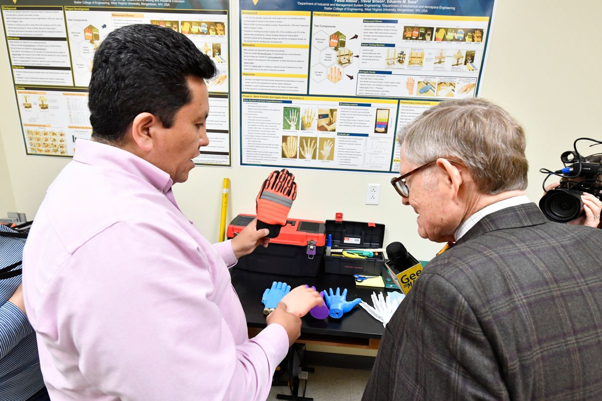 Two men look at safety gloves