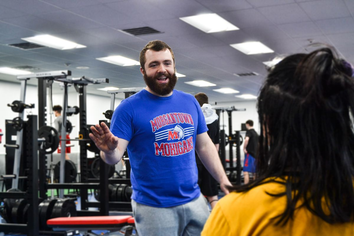A man in a blue t-shirt talks to someone in a gym